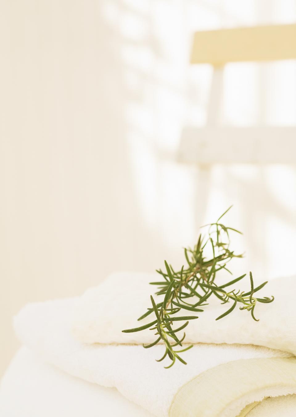 Zweigen Rosmarin und weiße Handtücher