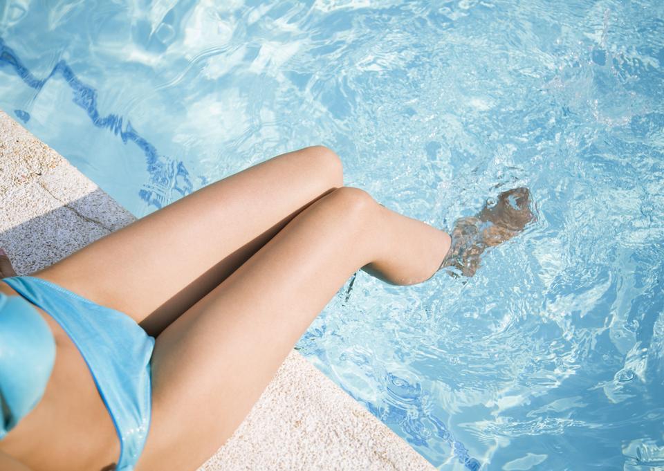 美丽的女人的腿在泳池