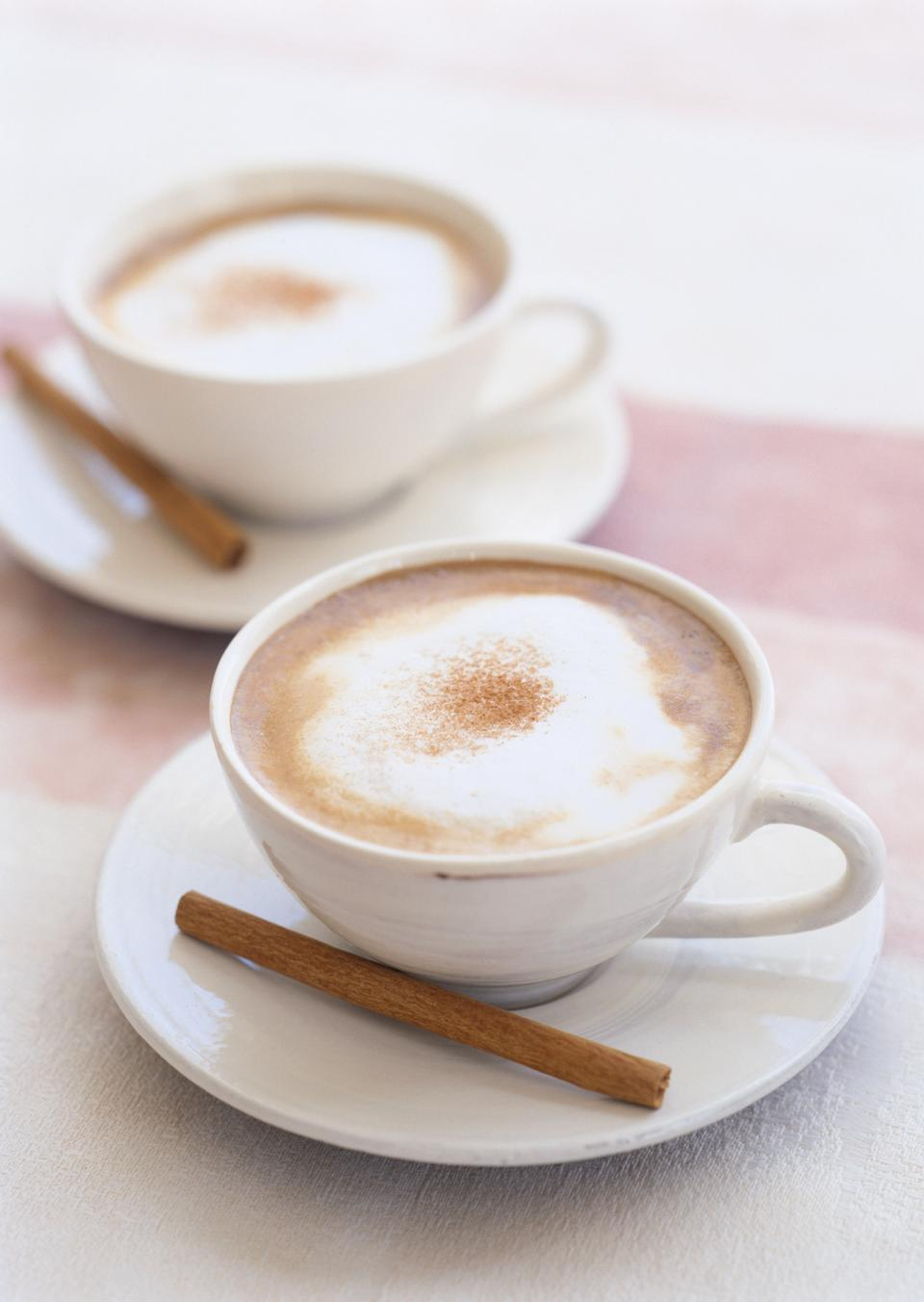 Two cups of cappuccino with cinnamon stick