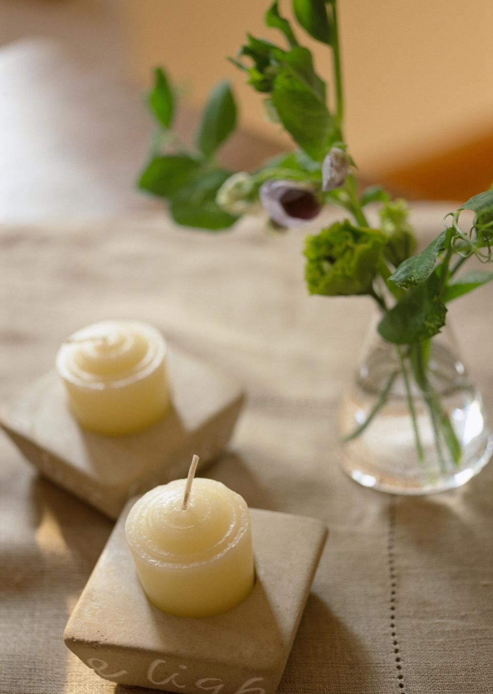 Филиал цветов в вазочке, белые свечи на стенде