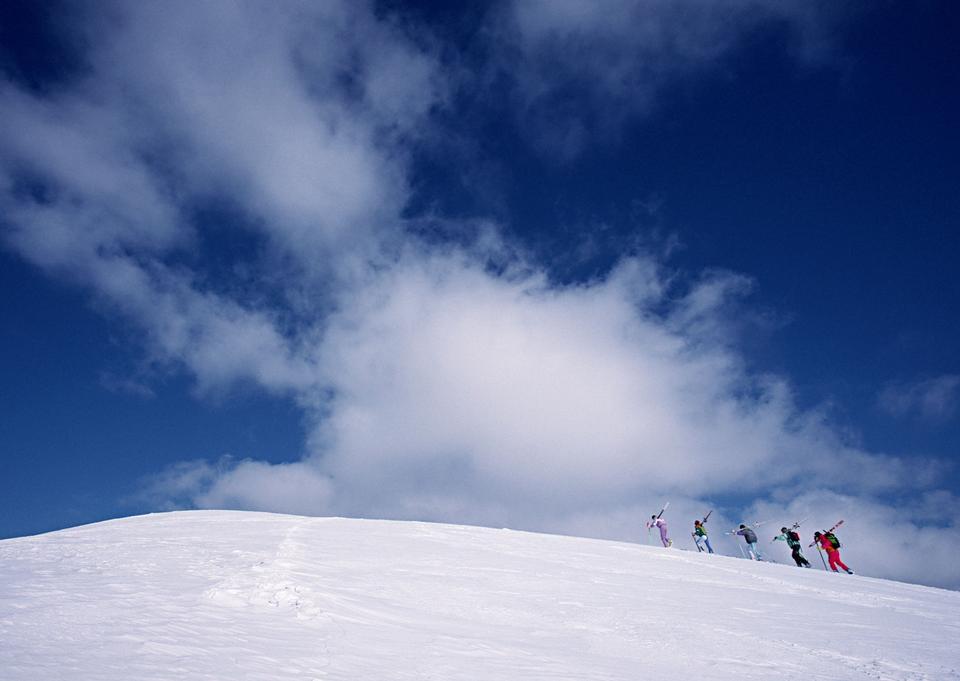 クライマーは、黒い服を着て、雪の斜面を登ります