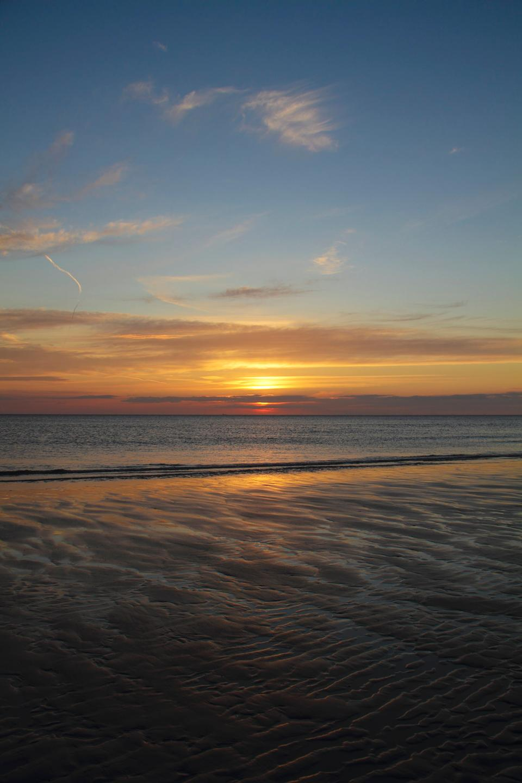 與反射的雲彩的沿海日落