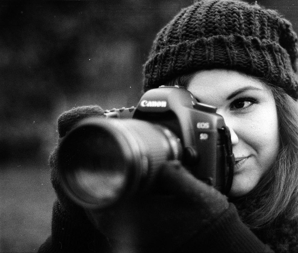 young woman photographing outdoors in winter