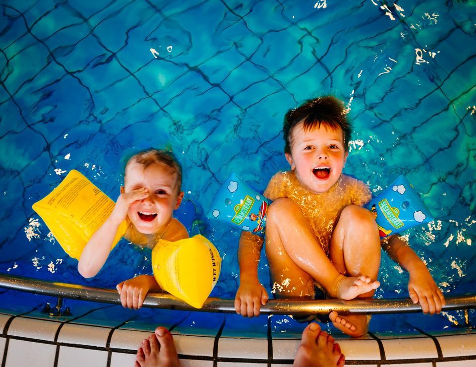 泳ぐことを学ぶスイミングプールクラスで幸せな子供たちの子供たちのグループ