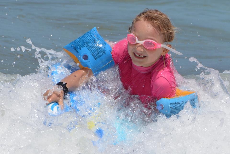 若いサーファー、サーフボード上の海で幸せな若い女の子