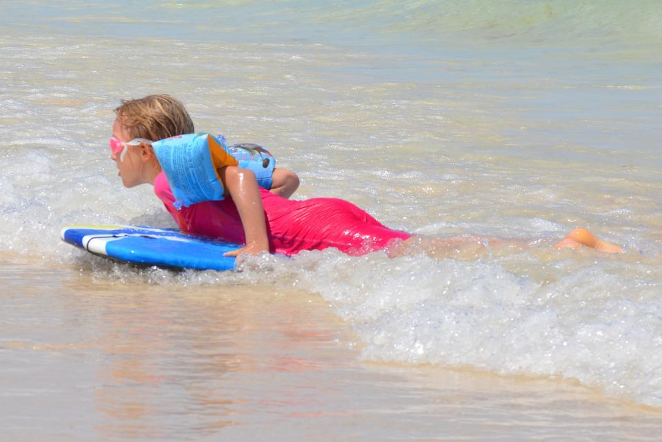 Happy young girl in the ocean on surfboard