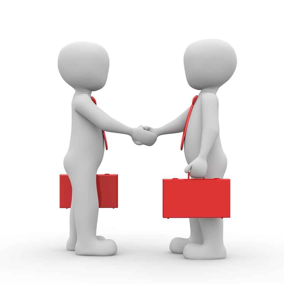 Business meeting at the table shaking hands conclusion
