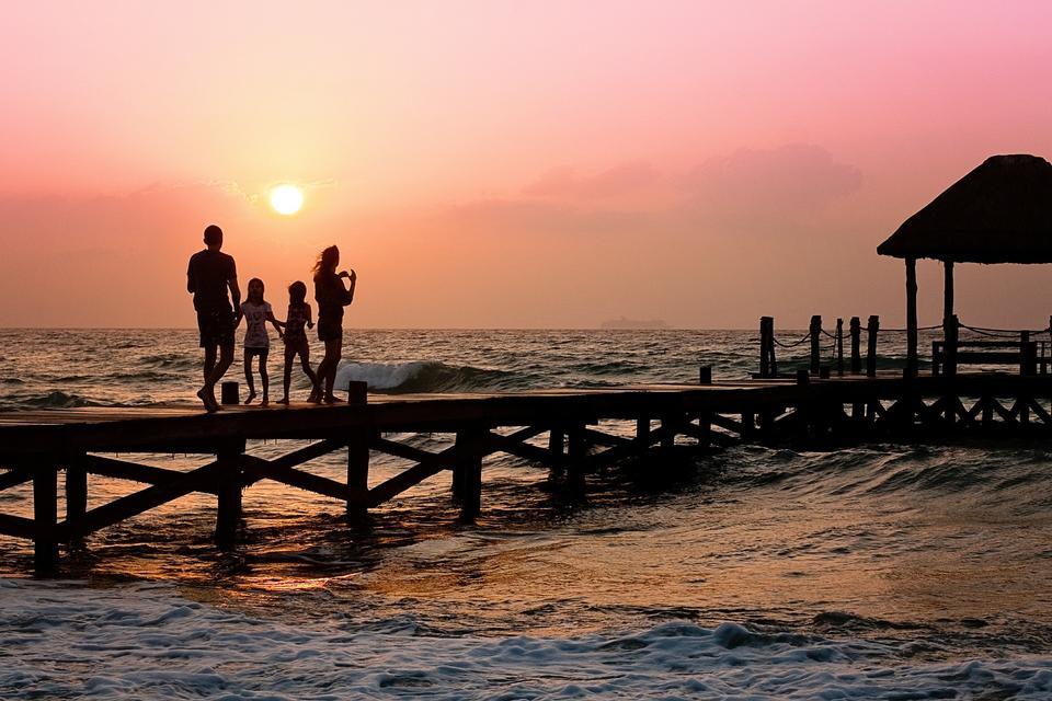 Familie von drei auf hölzernen Steg am Meer
