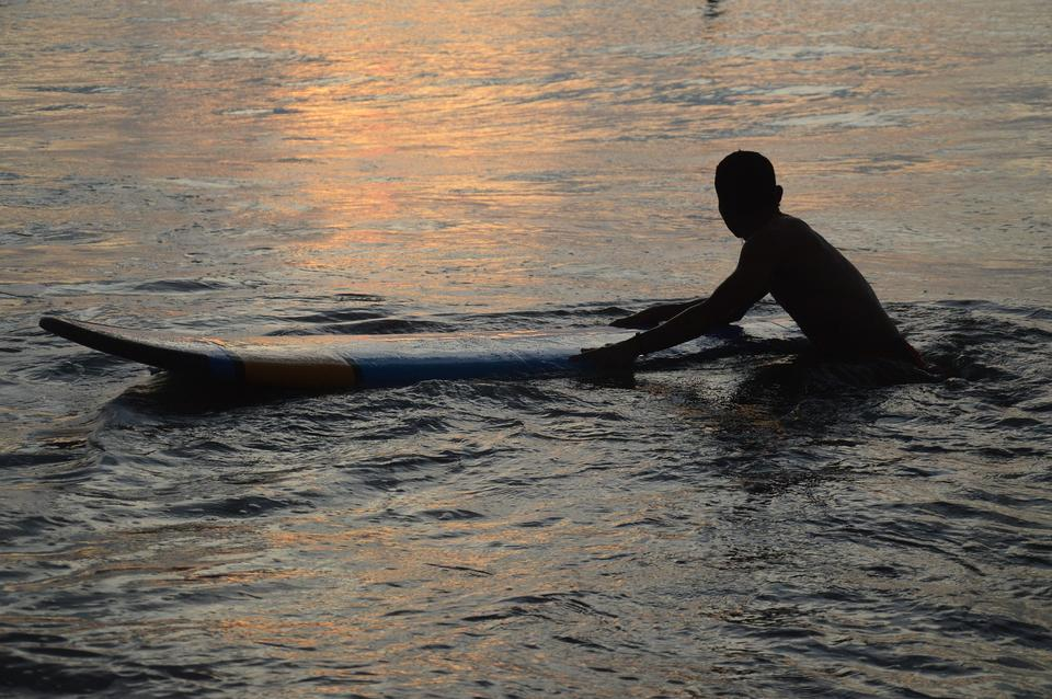 小男孩玩乐游泳上冲浪板假期