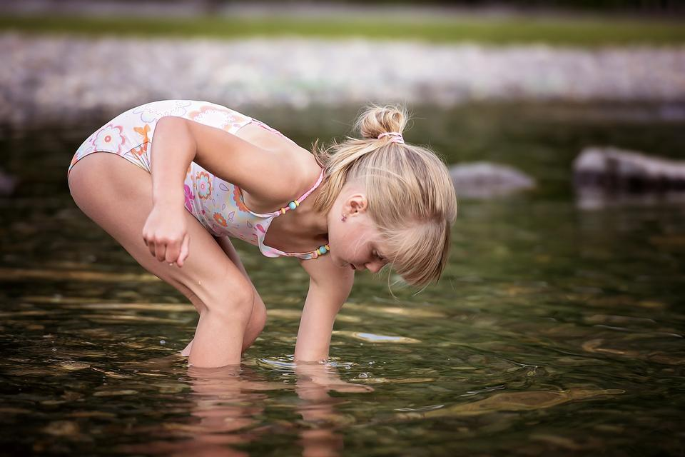 girl playing in outdoor swimming pool