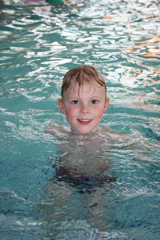 Netter Junge mit Brille im Pool
