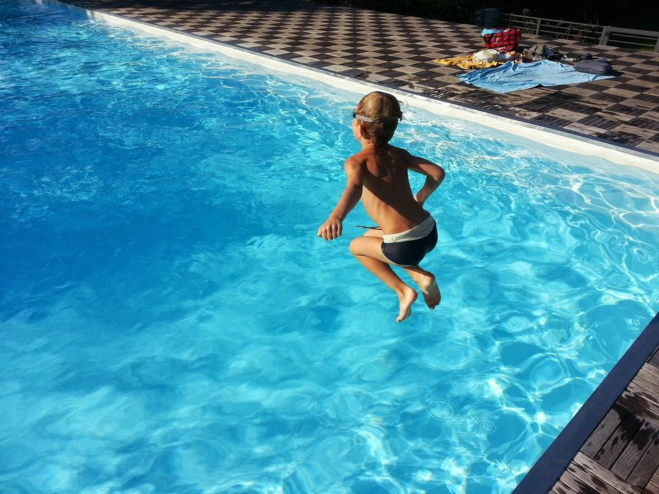 Close up of young boy swimming in pool.