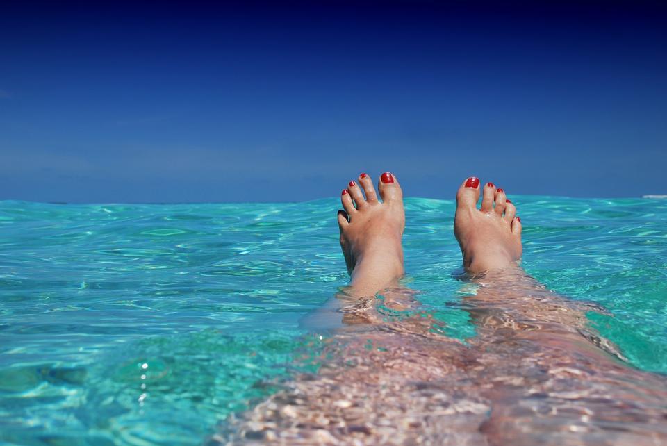 Woman feet close-up relaxing on beach, enjoying sun