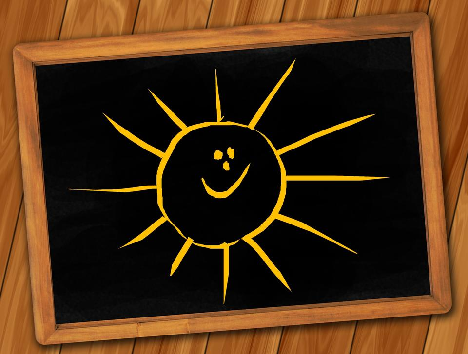 Black chalkboard. Drawn smile sun