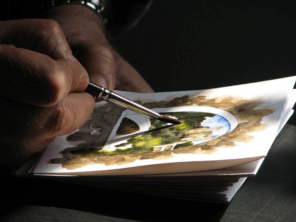 Close-up view of highly gifted painter while he is painting his p