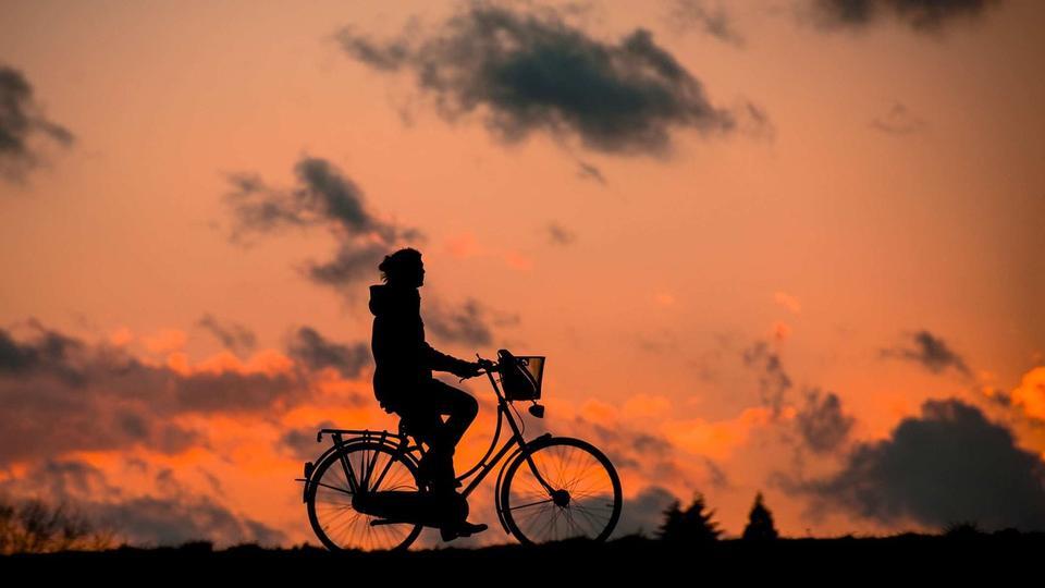 vététiste silhouette dans le lever du soleil avec la réflexion dans l'eau