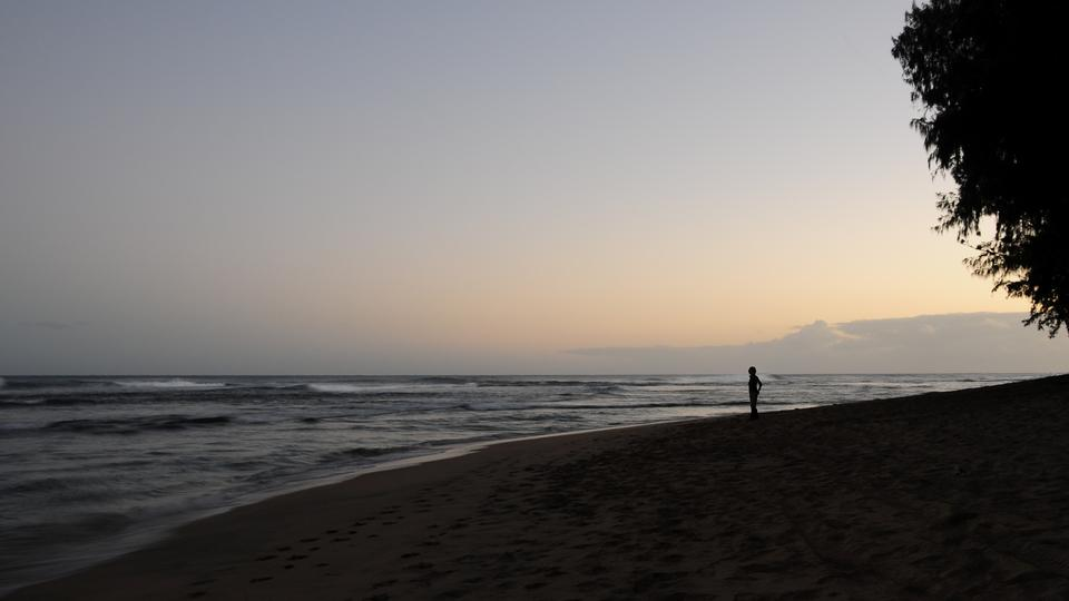 Silhouette of a person walking on the beach on Kauai