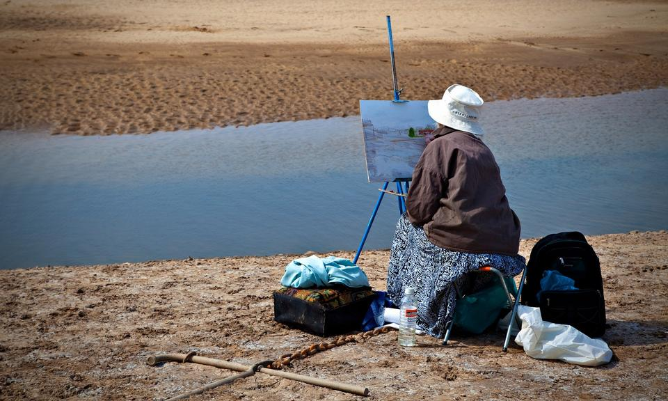 Female hand holding palette and easel with canvas on beach