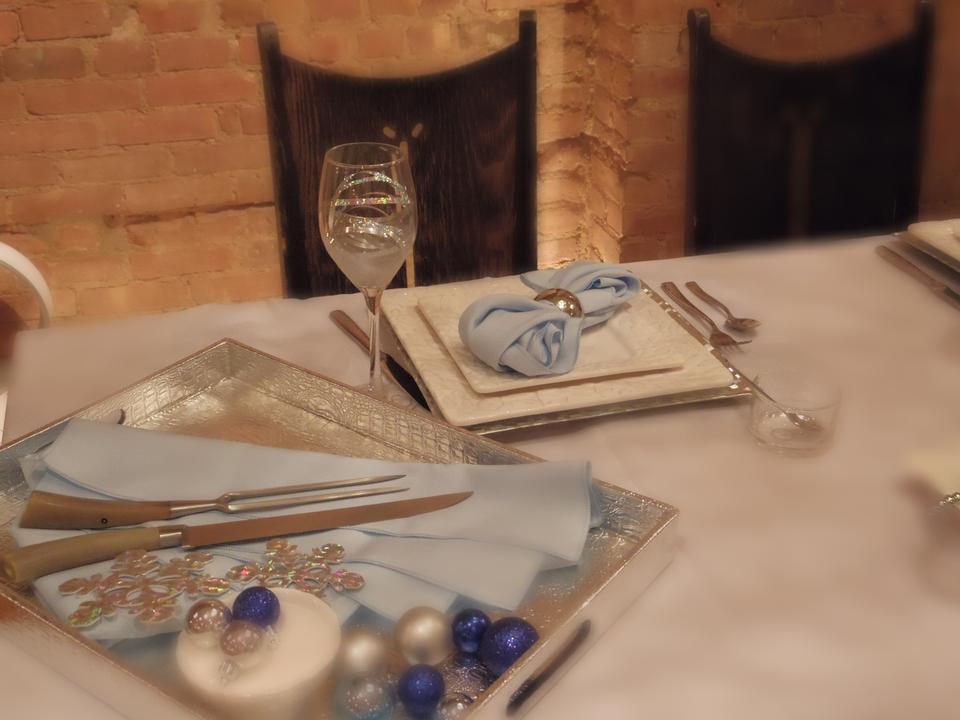 高級レストランのディナーテーブルの場所の設定:ナプキン、ワイングラス、PL