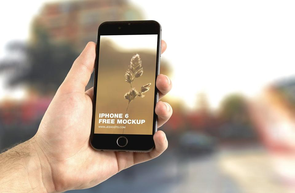 Man hand holding smart phone against fall background