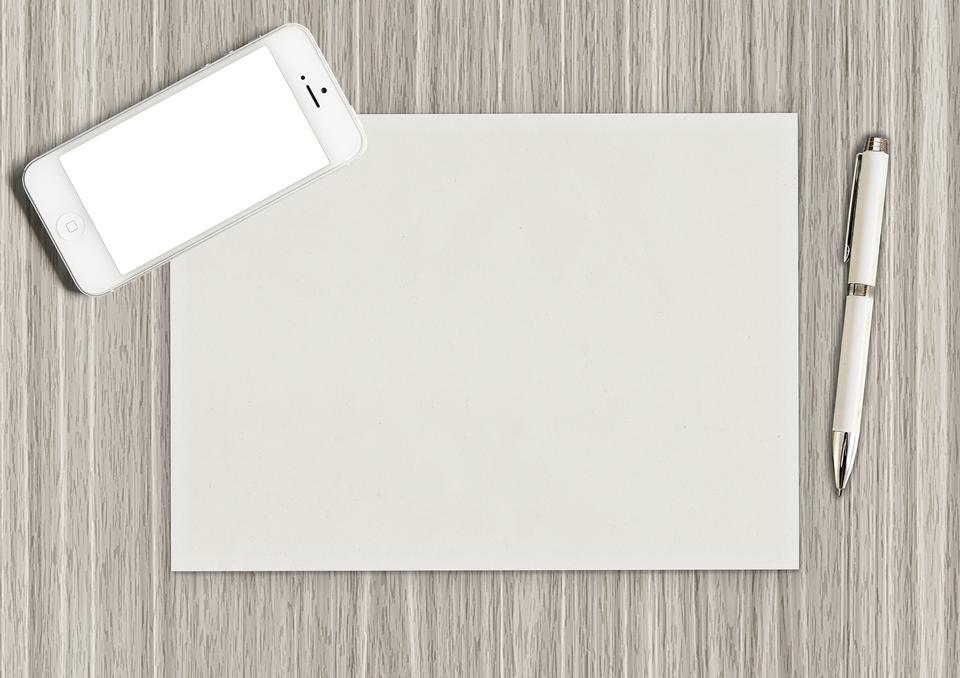 オフィス木製のテーブルの上にペンや鉛筆でメモ帳の空白
