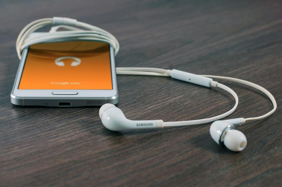 Smartphone avec des écouteurs, sur la table en bois