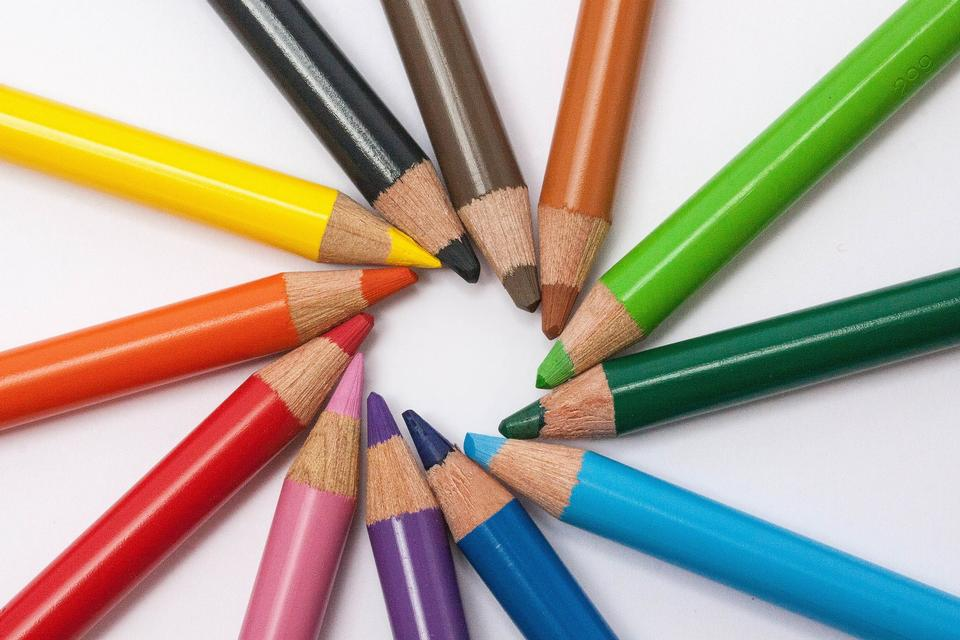 Color pencils in arrange in color wheel colors on white backgroun