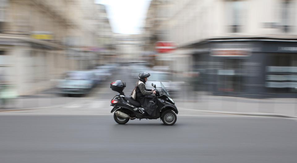 coureur de scooter dans le trafic urbain en mouvement flou