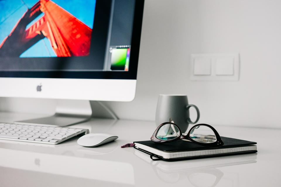 Mac computer on desk with cup and glasses