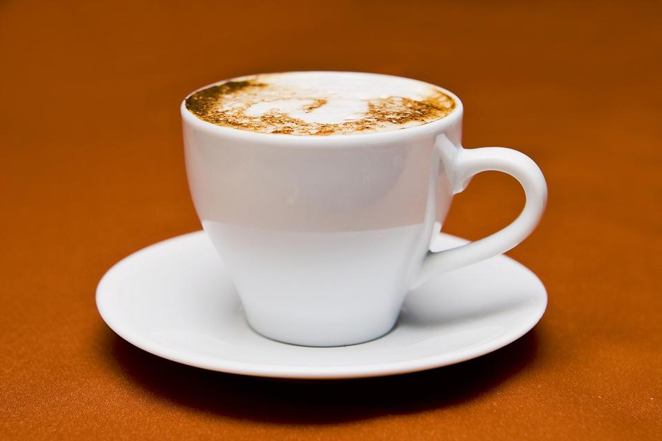 Cappuccino in a white cup on a white plate