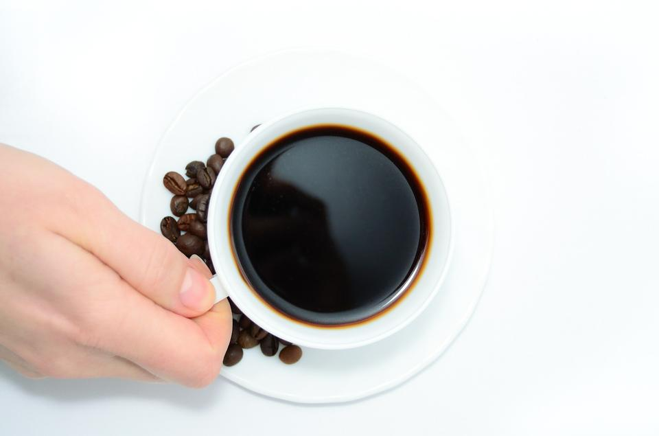White coffee cup with coffee bean on plate