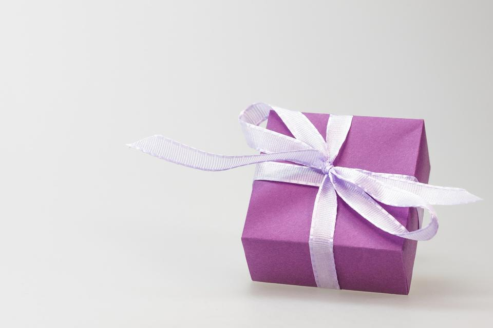 A violet gift with a red ribbon and a bow