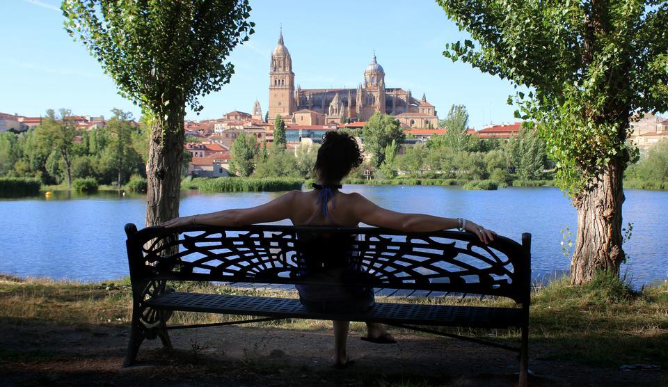 年轻的女士坐放松公园的长椅上