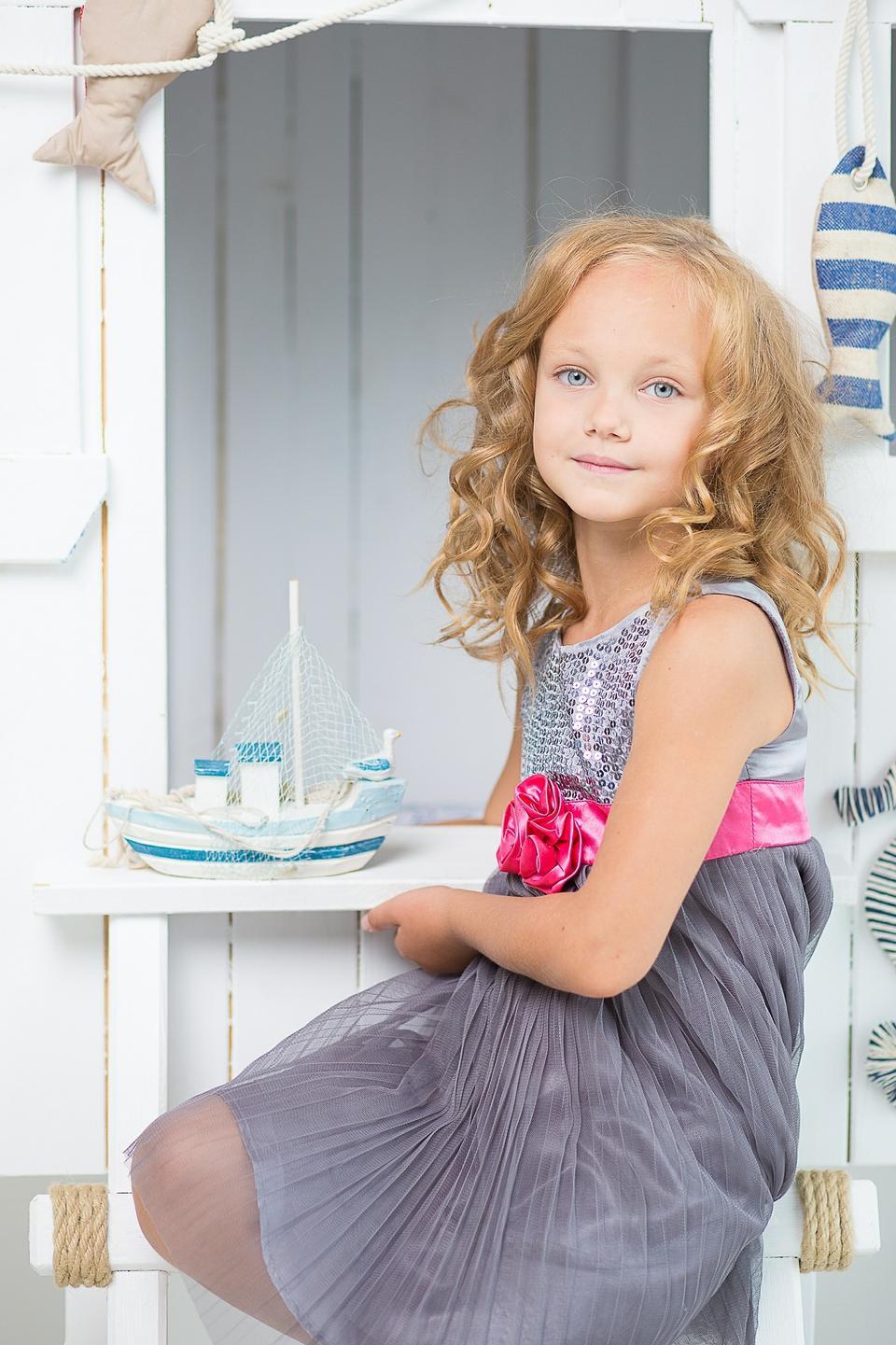 一个可爱的小女孩坐在梳妆台