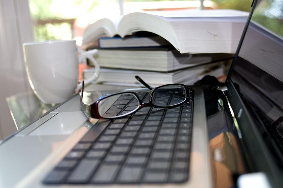 Black framed upside down glasses on the computer keyboard