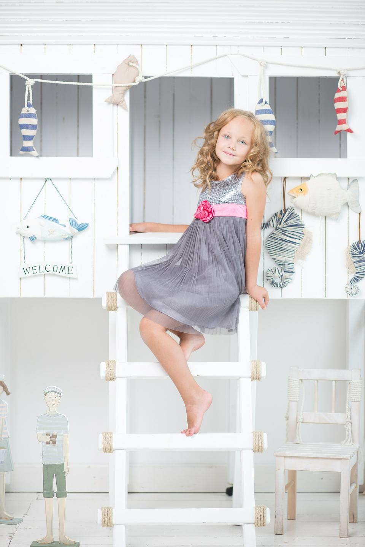 Menina bonito pequena que senta-se na escada no quarto dela