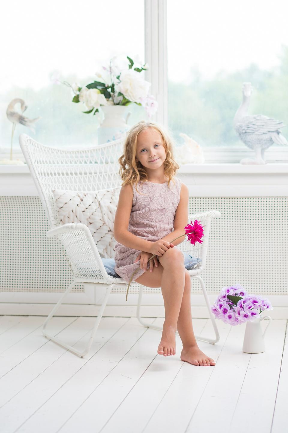 Little cute girl sitting on little chair