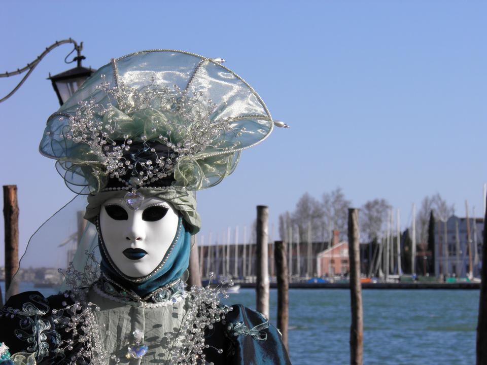Costumed people in Venetian mask on during Venice Carnival