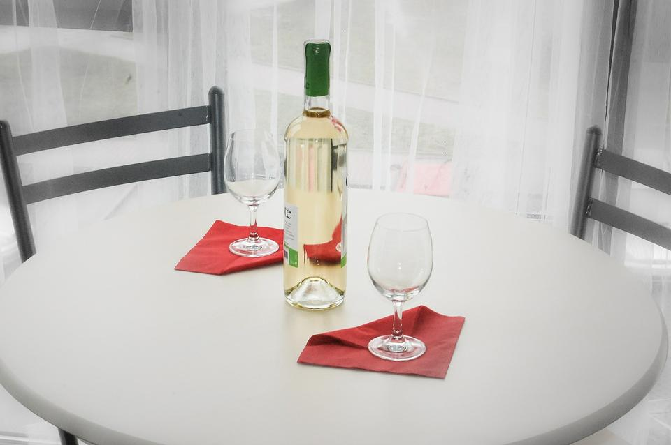 Table setting with empty plate, wine glass and  wine bottle