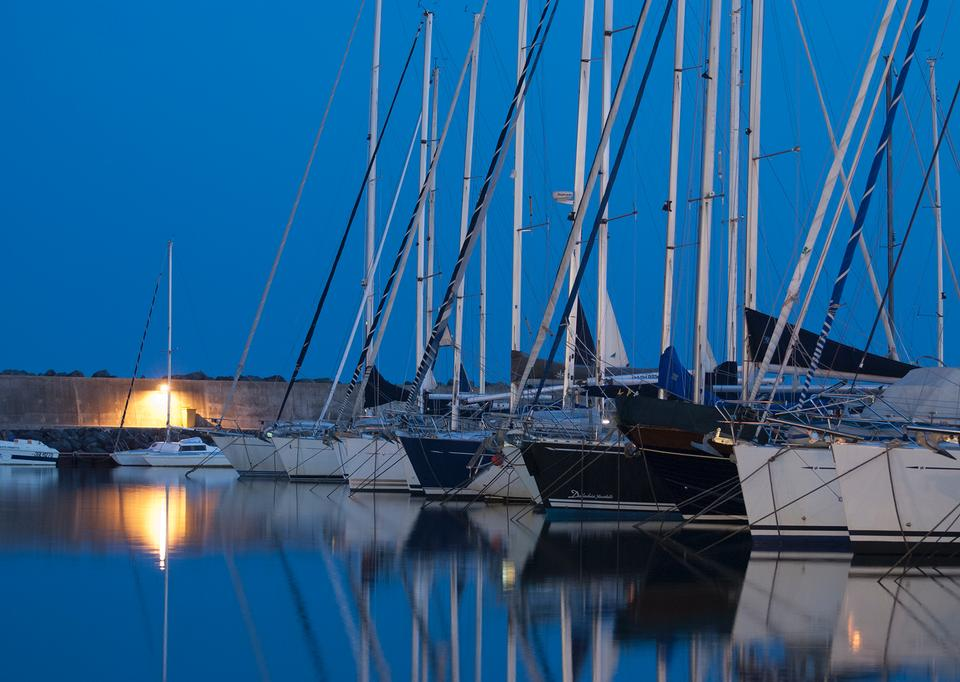 Barco de vela en el puerto deportivo en la puesta del sol