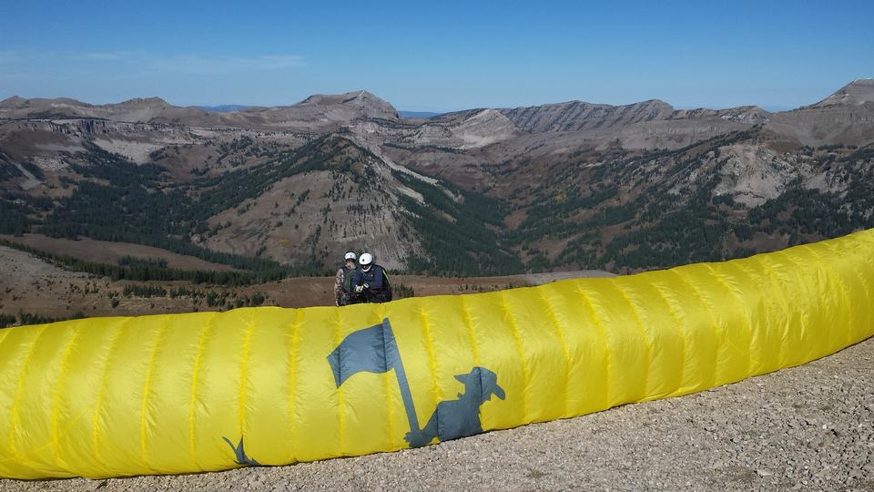 Paraglider sailing above Jackson Hole, Wyoming with blue sky