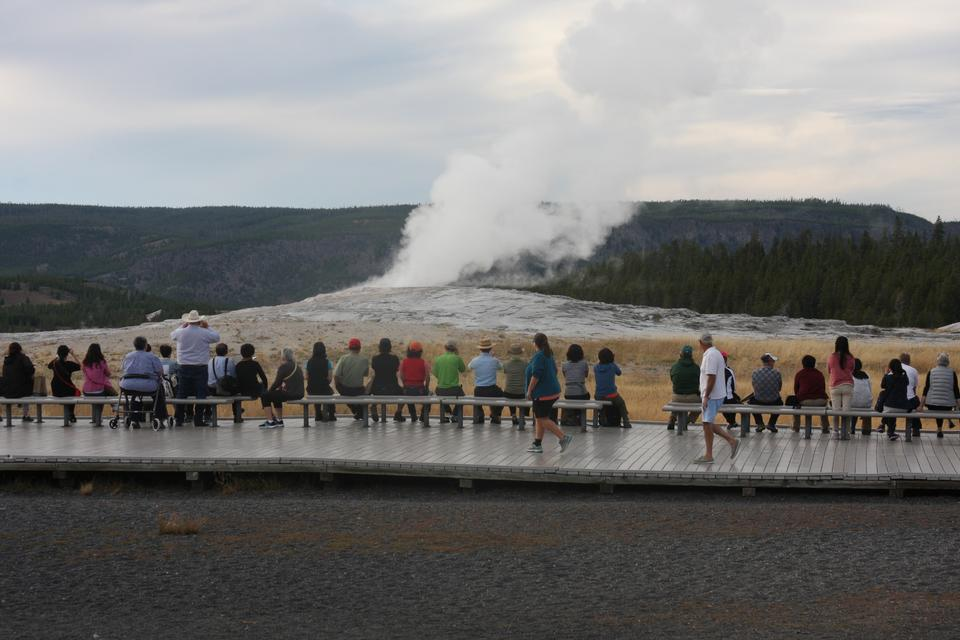Tourists watching the Old Faithful erupting in Yellowstone