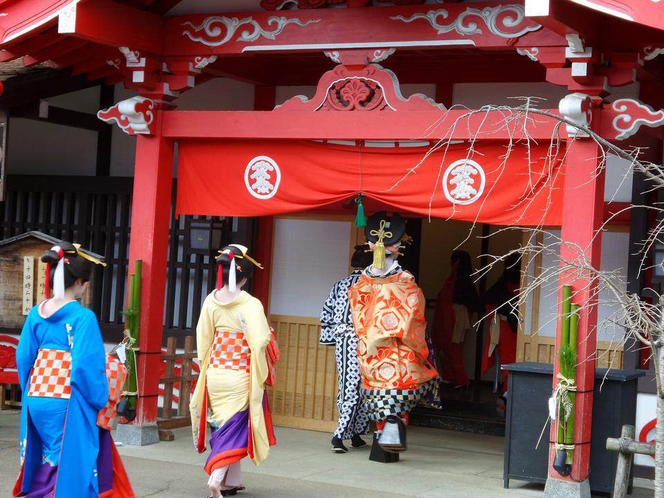 Three geishas walking on a street