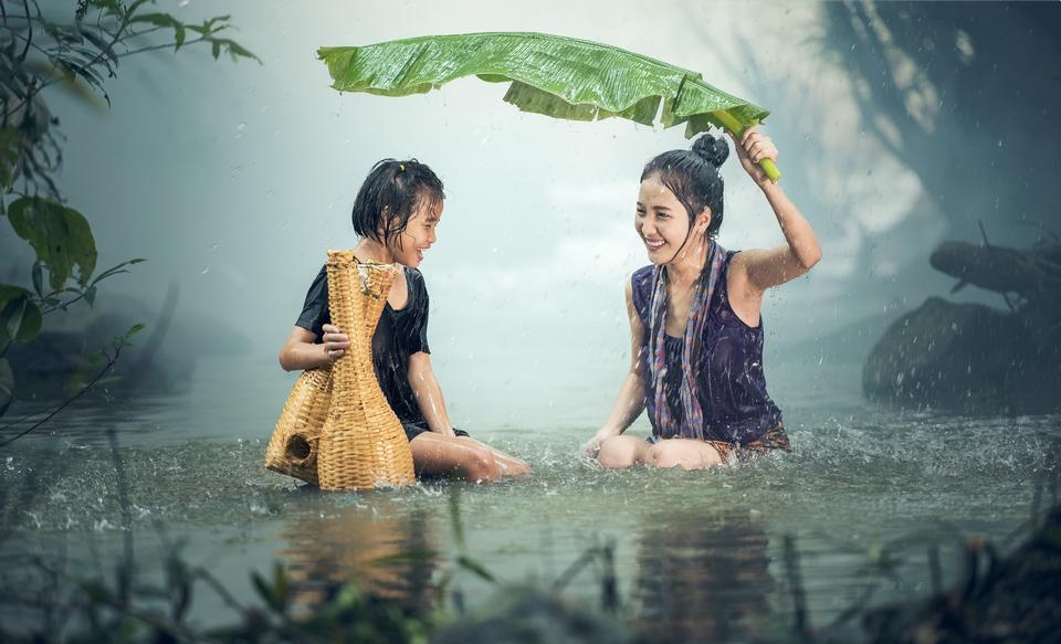 Two girls hiding from the rain under a large leaf plants