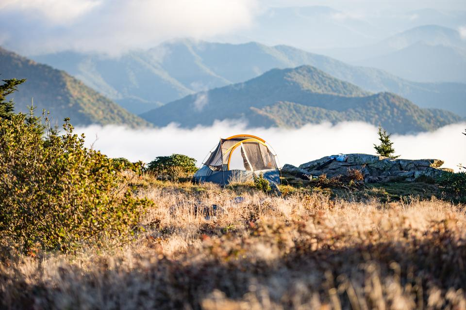 Camping Tent on Peach Leveled With Clouds Near Mountain