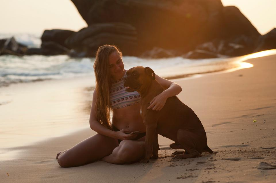 blond woman sitting on sand with dog