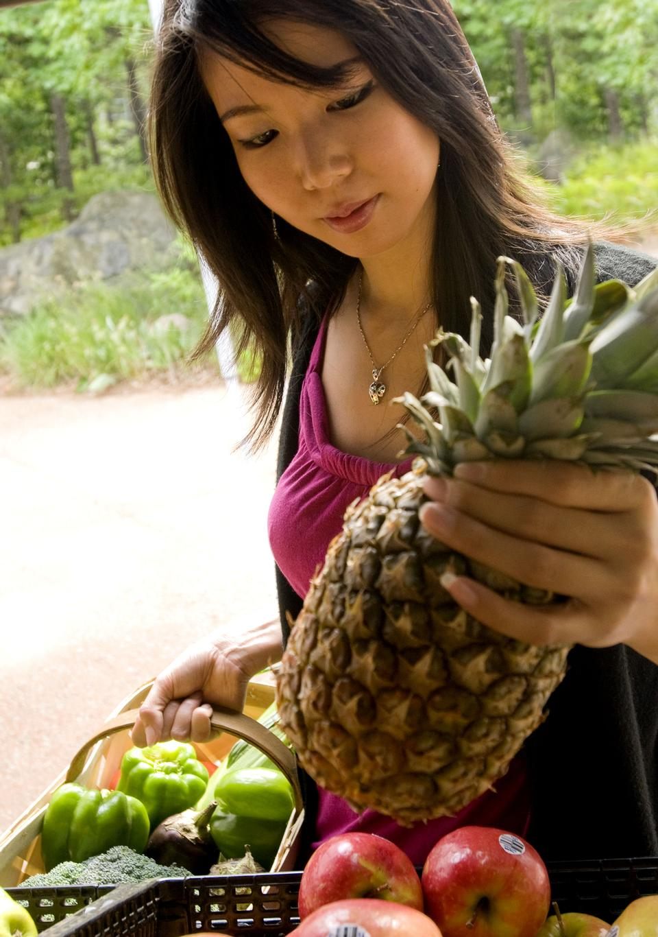 Happy young woman showing pineapple