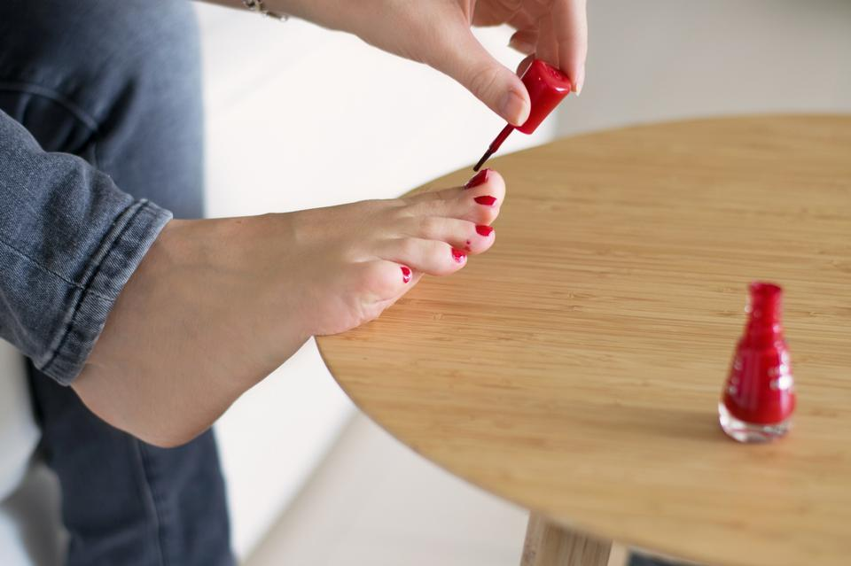 Woman with manicured fingernails painting her toenails