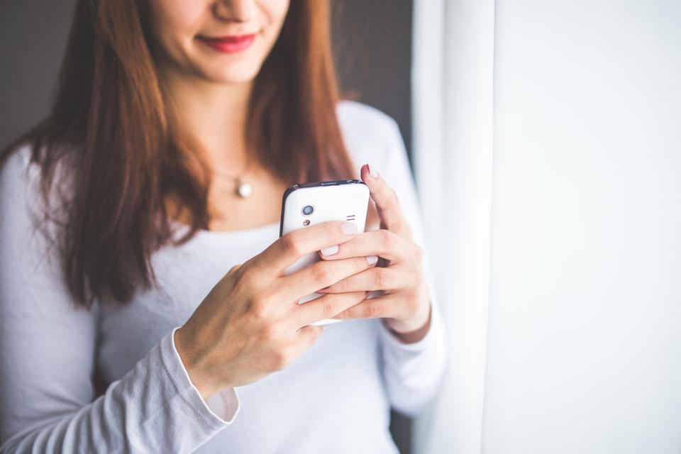 Close up of women's hands holding cell Phone