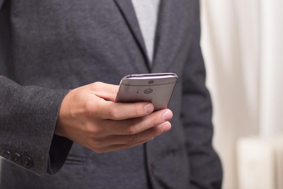 Gros plan des mains de l'homme tenant un téléphone cellulaire